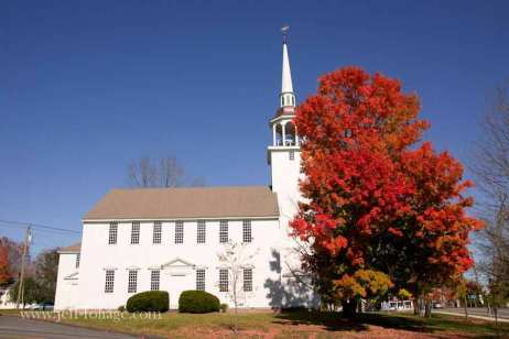 a single gigantic orange and red Maple next to a church in Brooklyn Connecticut on route 69