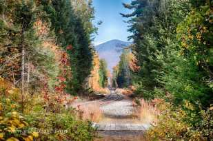 railroad tracks leading off into the mountains through the fall colors of New Hampshire