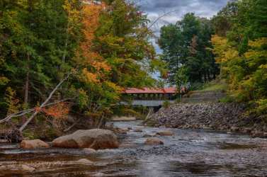 The Saco river covered bridge as seen from the Swiftriver covered bridge with fall foliage colors starting to develop.