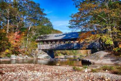 The Sunday river covered bridge also known as the Sunday River covered bridge with bright fall foliage around it.