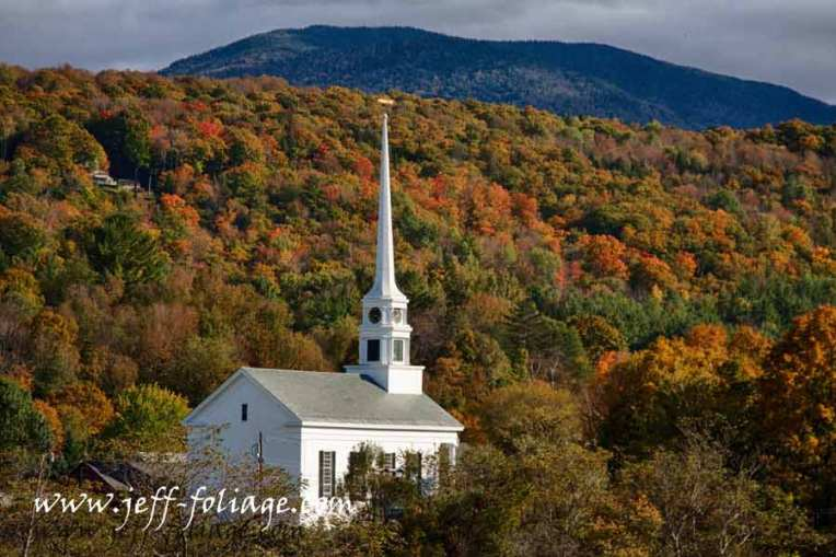 Stowe Vermont white steeple against a hillside of autumn color