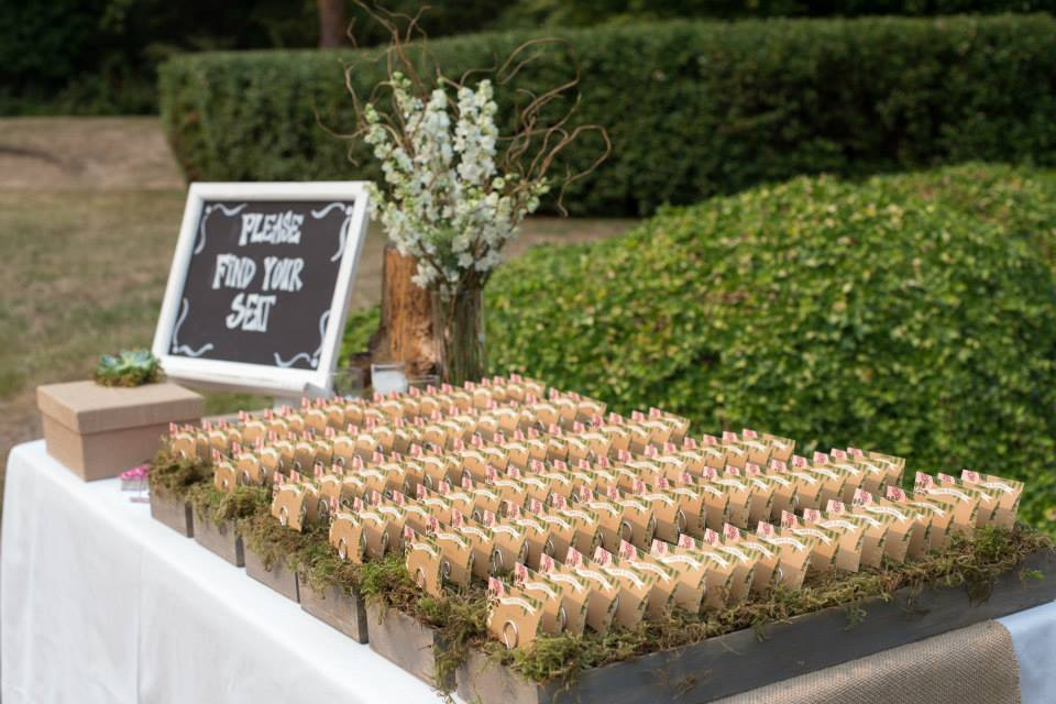 Escort cards in wood boxes lined with moss.