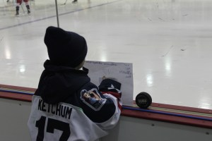 A young fan watches on intently as the Riveters skate past.