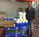 Shai Davaroff posing with donated Strauss dairy products in honor of Shavuot food drive