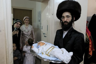 A Chassidic Jewish man holds aloft a baby boy named Chaim Mordechai Gross in a 2009 Pidyon HaBen ceremony in Israel. (Illustration Photo)