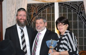 (L-R) Presentation of handmade menorah from Zion Orphanage's Rav Baruch Rakovsky to hosts Rafi and Esther Katz.