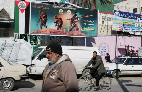 Palestinians walk in front of a billboard Hamas in Rafah refugee camp in the southern Gaza Strip