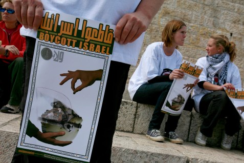 Internatinal peace activists holds posters calling to boycott Israel during a protest outside the Damascus Gate in Jerusalem