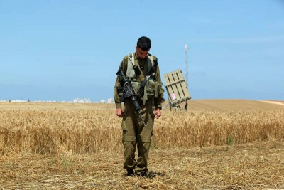 An Israeli soldier standing near the Iron Dome anti-rocket system