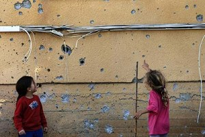Young Kibbutz girls Kibbutz examine the shards on the wall by a qassam rocket.
