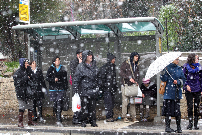 Israelis wait for a bus on a snowy winter day in Jerusalem. (archive)
