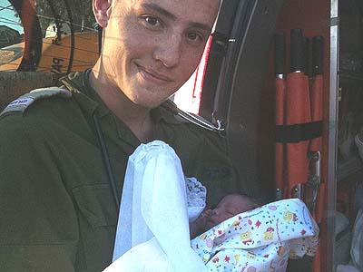 IDF Paramedic with newborn Palestinian baby.