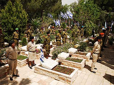 Soldiers stand at attention in front of the graves of the fallen at Mt. Herzl, Israel's national military cemetery.