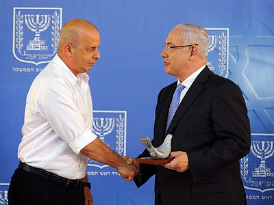 Yuval Diskin (L), receiving a farewell gift from Prime Minister Benjamin Netanyahu at the end of his term as Shin Bet chief.