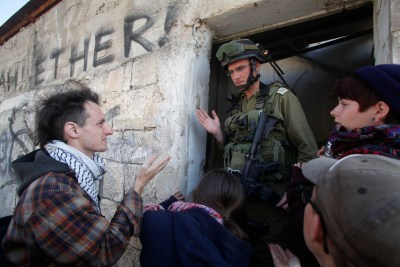 Israeli soldier is blocking left wing activist from entering a house in Hebron.
