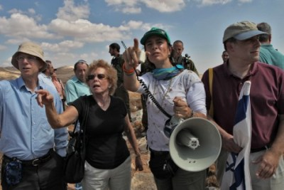 Activist Nadia Matar (center, with megaphone) with American guests at the Jewish settlement of Bnei Adam.