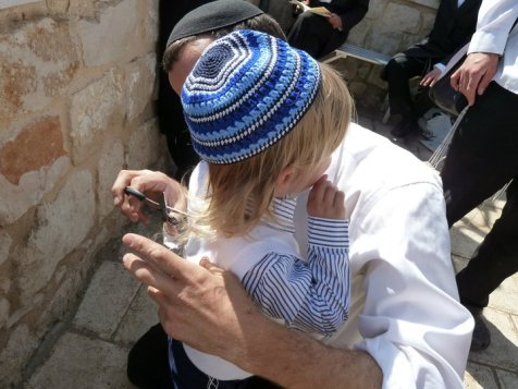 As thousands of Jews gather at Meron, fathers give their 3 year old sons a first haircut at the gravesite of Rabbi Shimon Bar Yochai.  Jewish culture and tradition is flourishing and joyous on Lag B'Omer in Israel.  (Photo credit: Yishai Fleisher)