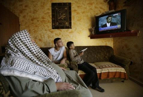 An arab family watching President Obama speak on TV