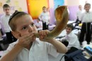 Student blowing a shofar