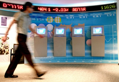 A man walks past a baord showing stock fluctuations at the Tel Aviv stock exchange.