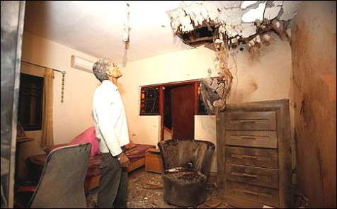 A resident of Sderot in southern Israel examines the damage in his living room after a Kassam rocket fired by terrorists in Gaza hit his house. Another rocket fell on his daughter's bed. The man's family was in a bomb shelter during the shelling.