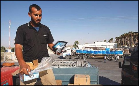 Can you launch a missile with this iPad? Palestinian worker inspecting the contents of trucks carrying supplies into Gaza from Israel.