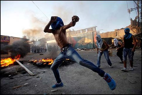 Masked Palestinians throw stones at Israeli security forces during clashes in the Shuafat refugee camp on the outskirts of Jerusalem.