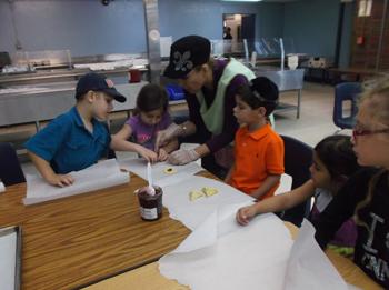 Morah Malka prepares hamentashen with PreK students.