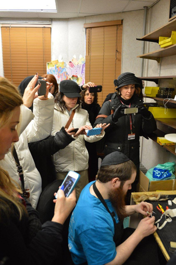 Guests at the recent International Conference of Shluchos in Crown Heights watching a sofer at work.
