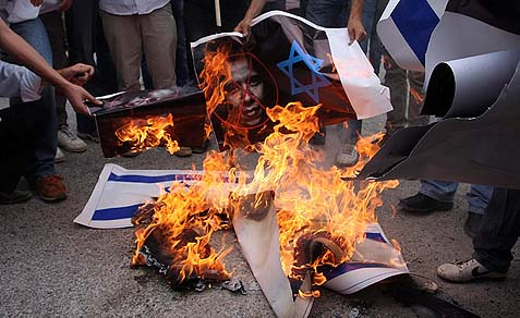 Palestinian protesters burn an Israeli flag and a poster of U.S. President Barack Obama in the village of Nabi Saleh, near Ramallah.