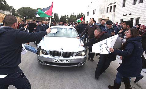 Palestinians surrounding the British Consul General in Jerusalem Vincent Finn's car, as he is forced to leave the Birzeit University campus in Ramallah, March 5, 2013.