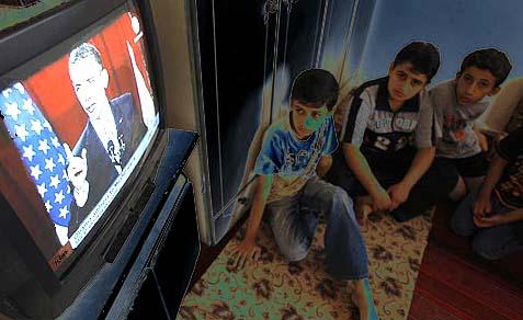 Palestinian boys listen to President Barack Obama's speech at Cairo University.