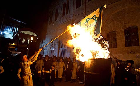 Anti-Zionist Haredim burning the Israeli national flag.