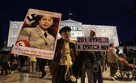 A protester in front of the Greek parliament holds up a poster depicting German Chancellor Angela Merkel as a Nazi.