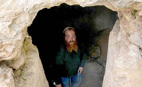 Archaeologist Benyamin Storchan standing at the bottom of the steps in the immersion chamber.