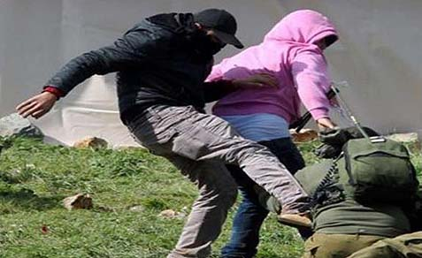 Arabs kicking IDF soldier on the ground.