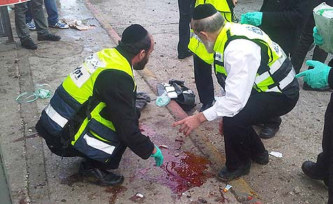 ZAKA medical rescue workers clean blood off the ground at the scene of where a bomb exploded, injuring 25 people, near the Central Bus Station in Jerusalem. March 23, 2011.
