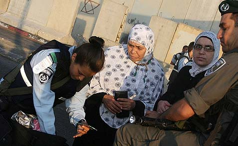 Israeli border police officers check Palestinian women who are waiting to cross the Qalandia checkpoint on the outskirts of Ramallah, as they head to the Al-Aqsa mosque compound in Jerusalem's Old City to attend the first Friday prayers of Ramadan (2012).