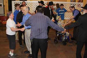 Liad (right, in wheelchair) dances with the men following Havdallah