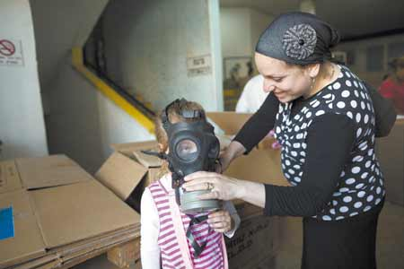 A young girl learns how to put on a gas mask in Jerusalem. The demand for gas masks has risen among Israelis as speculation grows about possible international military intervention in Syria.