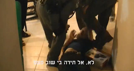 Police attack Boaz Albert as he lies on the ground.