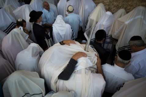 Men who are Kohanim -- members of the priestly caste -- spread their prayer shawls in preparation for the benediction of the Jewish Nation at the Western Wall.