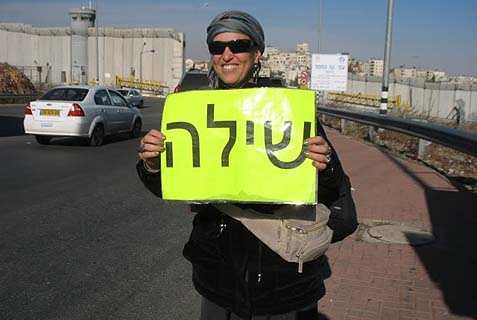 "Batya Medad holding a sign for her hometown, ""Shiloh"""