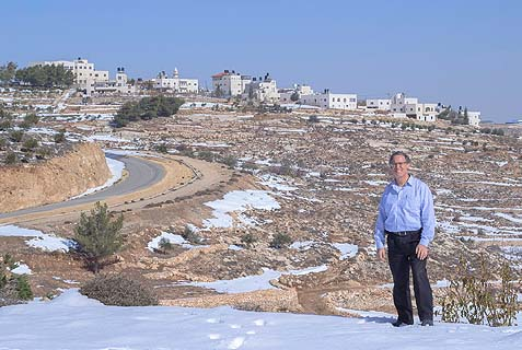 Dr. Yitz Glick in front of the Palestinian village he visits every week.