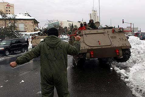 Israeli soldiers and emergency workers using an armored personnel carriers to clear snow covered roads in Jerusalem, December 14, 2013. This has been Israel's heaviest snow storm in 50 years.