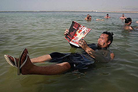 Reading the paper in the Dead Sea.