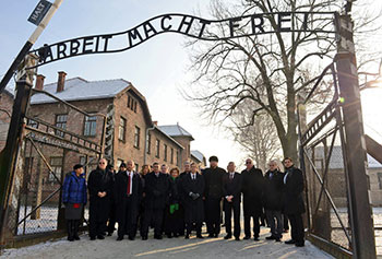 Knesset members walk through the entrance of Auschwitz.