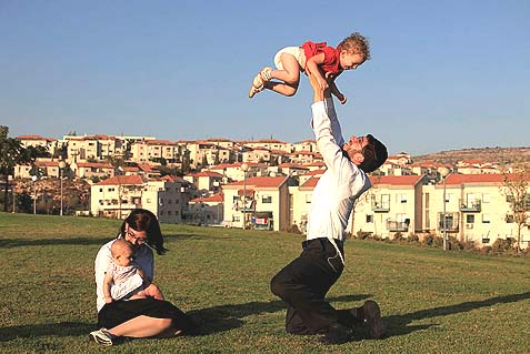Tali and Ephraim Messing play with their children in the Haredi settlement of Beitar Illit.