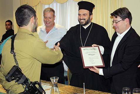 Father Gabriel Nadaf presents a soldier with an ICRF award.