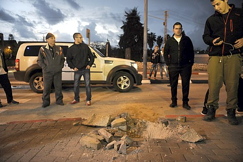 Israelis in Sederot examine the site of a Gaza rocket strike, on March 12, 2014.